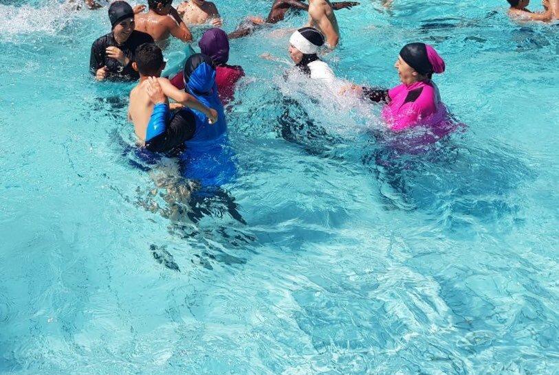 Donne musulmane in piscina col burkini per protesta contro il divieto: multate