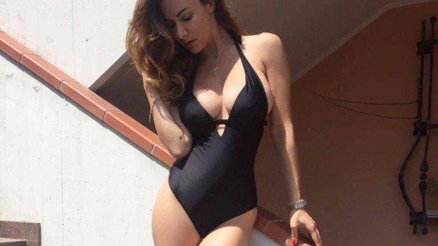 Melita Toniolo mimetizza le curve premaman con un costume nero